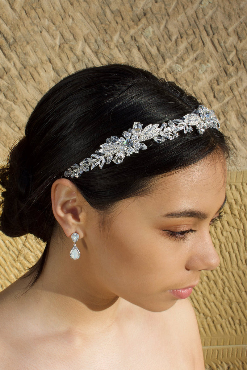 A dark haired model wears a Swarovski crystal crystal headband on the front of her head. The background is a stone wall.