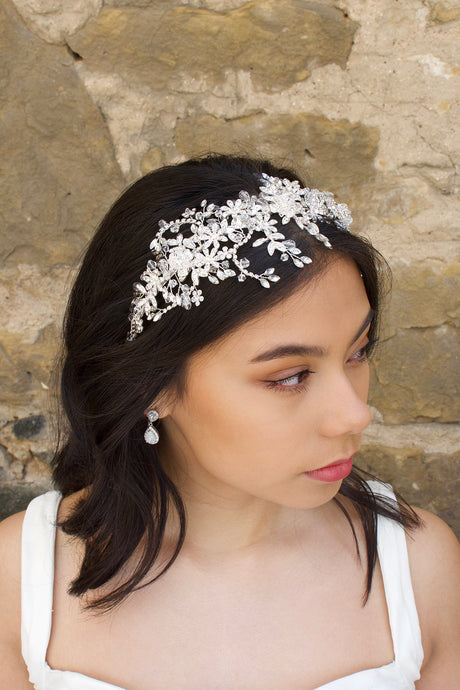 Model wears a silver crystal headband on her dark hair with a stone wall background