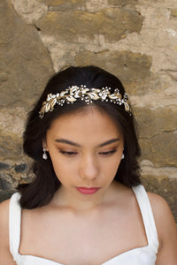 A front view of a model in front of a stone wall wearing a pale gold bridal headband on her forehead.