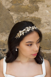 In front of a stone wall a dark hair Bride wears a soft gold bridal headband with tiny crystals