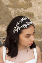 Load image into Gallery viewer, Black hair model looks to the side wearing a silver pearl handmade headband with a stone wall behind