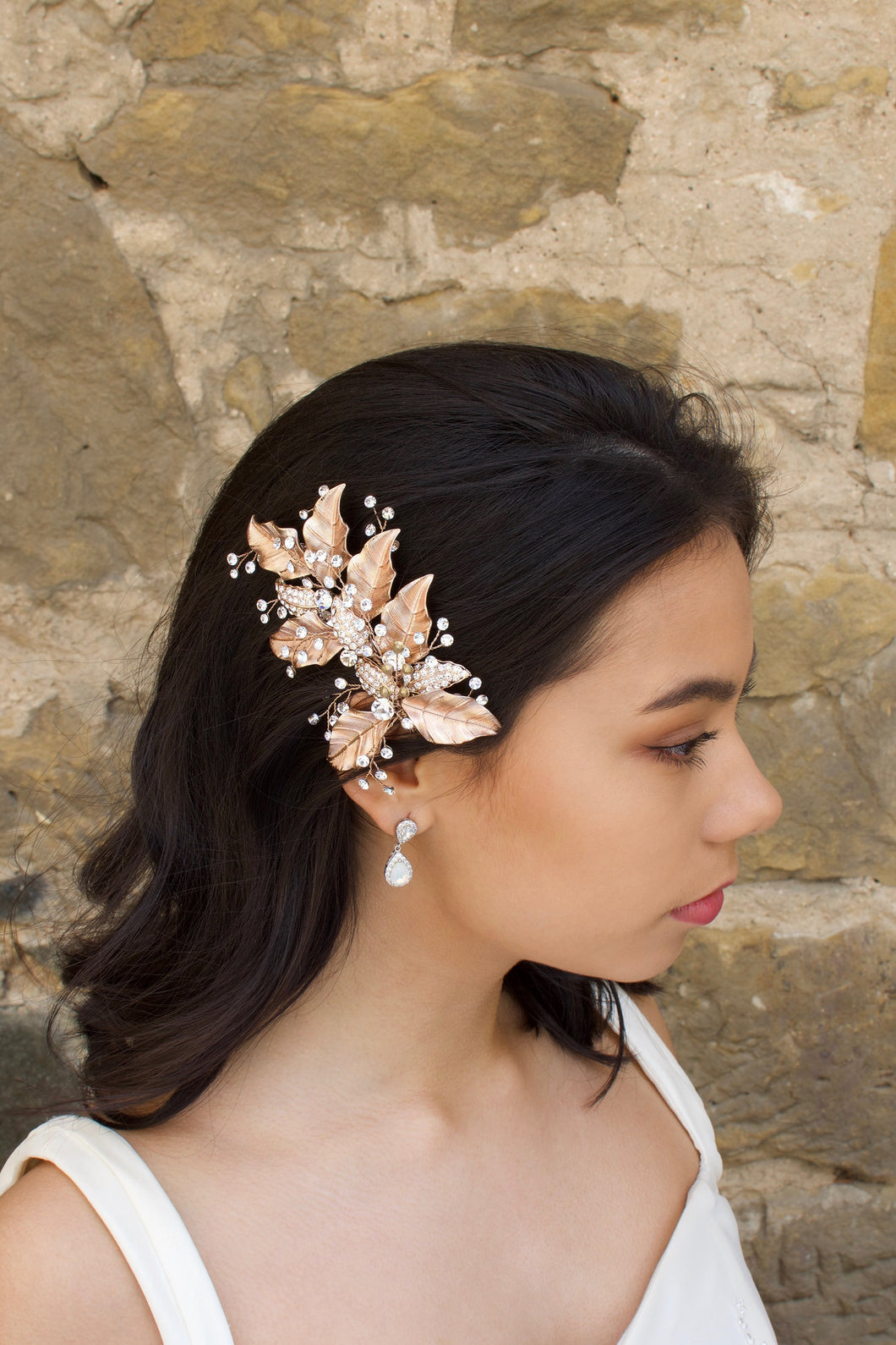 Rose Gold Leaves Side Comb with bright crystal sprigs worn by a dark hair model with a stone wall backdrop.
