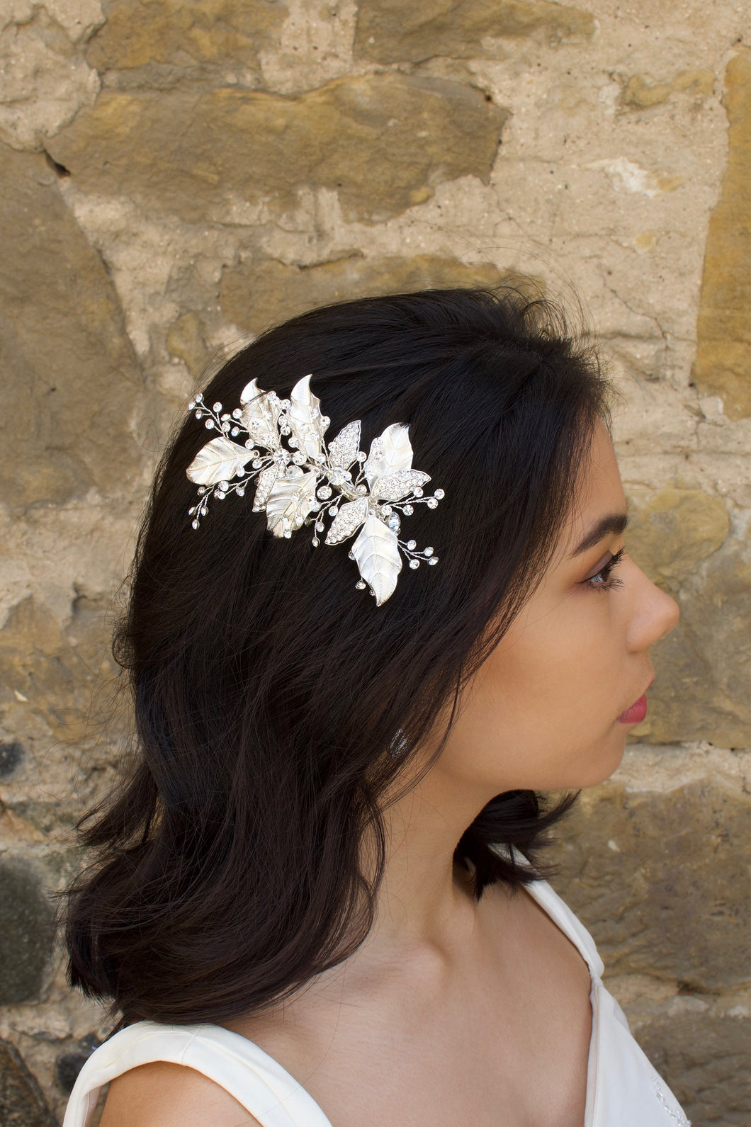 Silver Leaves Side Comb with sprigs of stones worn by a dark hair model with a stone wall backdrop