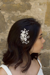 Silver Leaves and Crystals side comb worn by a dark haired model with a stone wall background