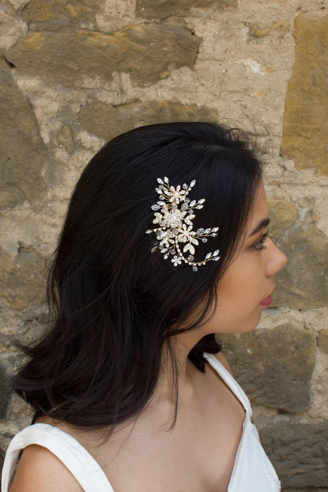 Gold Leaves and Crystals side comb worn by a dark haired model with a stone wall background