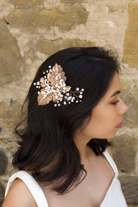 Filigree leaves side comb with freshwater pearls worn by a dark hair model in front of an old stone wall