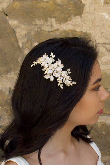 Pale Gold and peal side comb worn by a dark haired bride with a stone wall backdrop