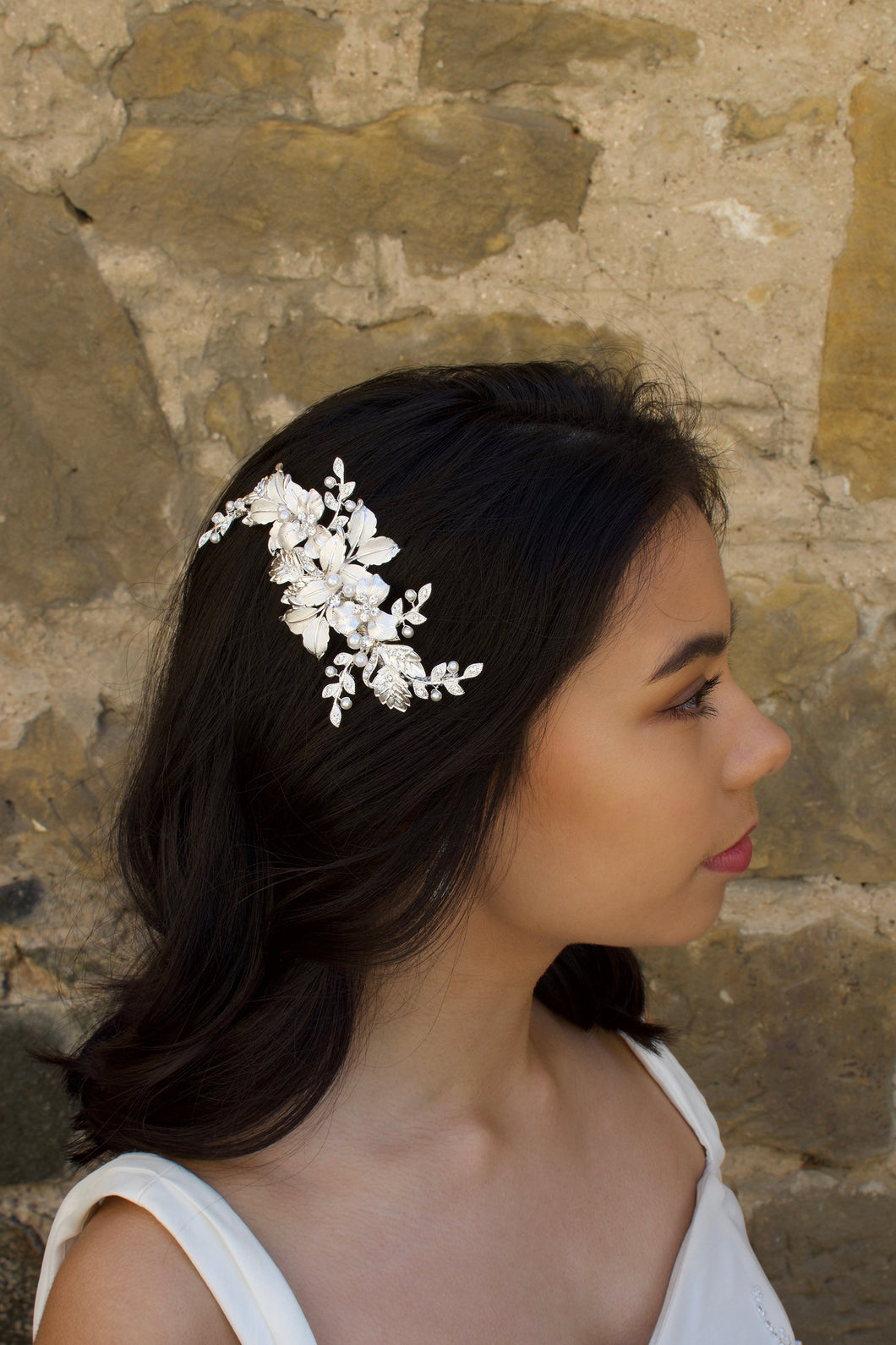 Soft Silver Side Comb with leaves and flowers worn by a dark hair bride with a stone wall backdrop