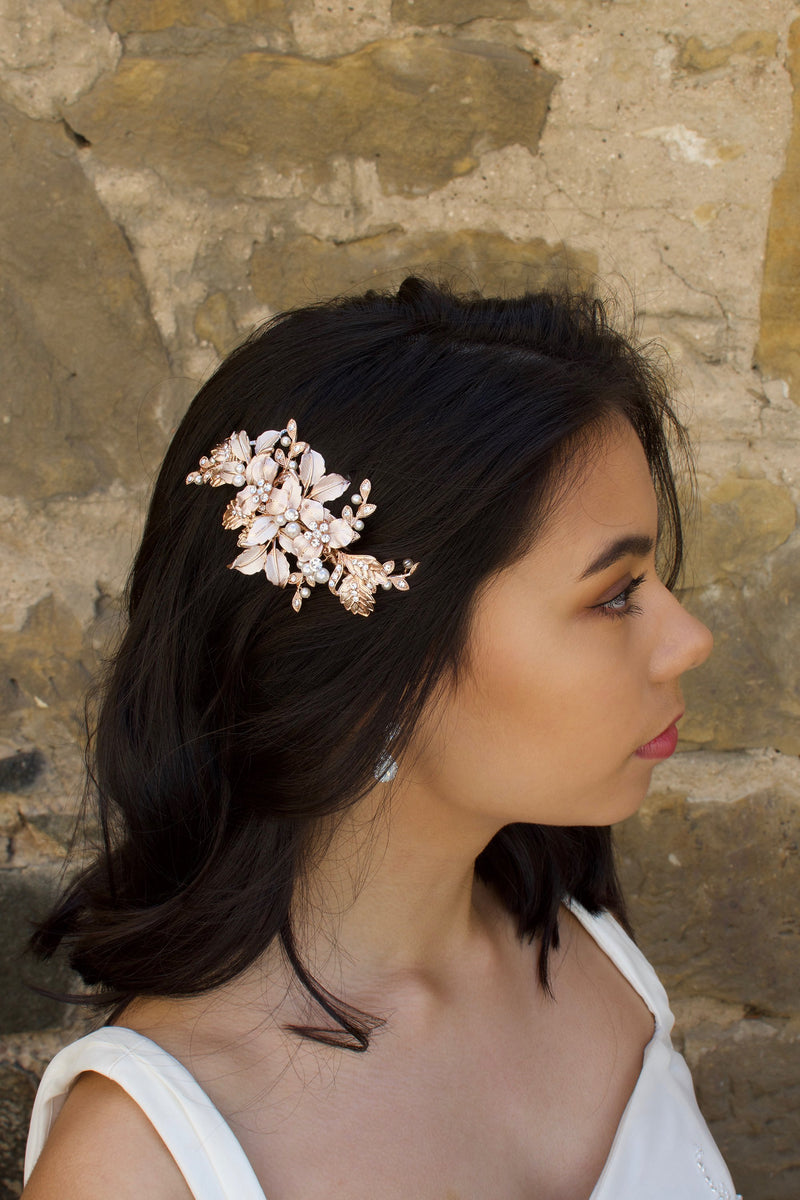 Pale Rose Gold Bridal Comb with leaves and flowers worn by a dark hair bride with a stone wall backdrop