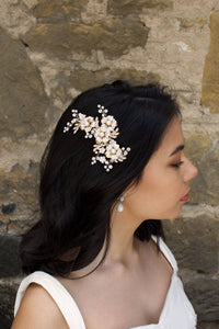 A Dark haired model wears a gold side comb of flowers with a stone wall background