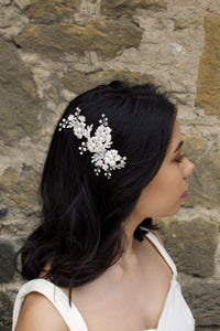 A Dark haired model wears a silver side comb of flowers with a stone wall background