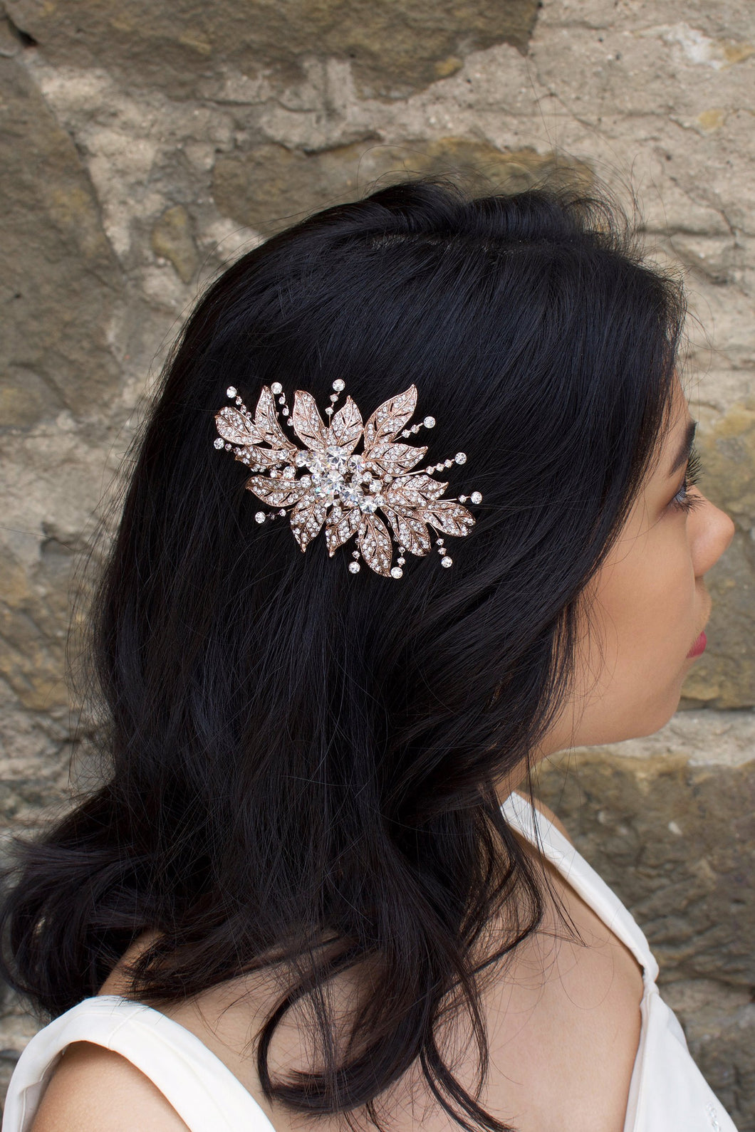 A back haired model wears a rose gold flower bridal side comb on the side of her head. A stone wall is the backdrop