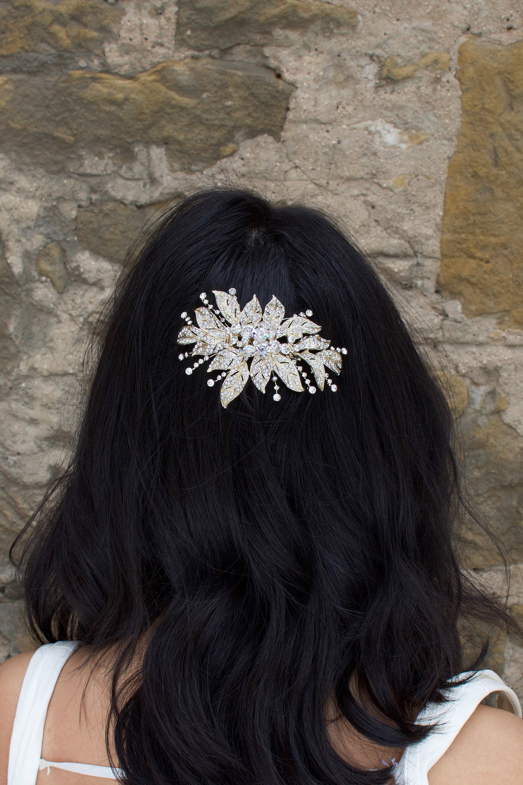 A back haired model wears a gold flower bridal side comb on the back of her head. A stone wall is the backdrop
