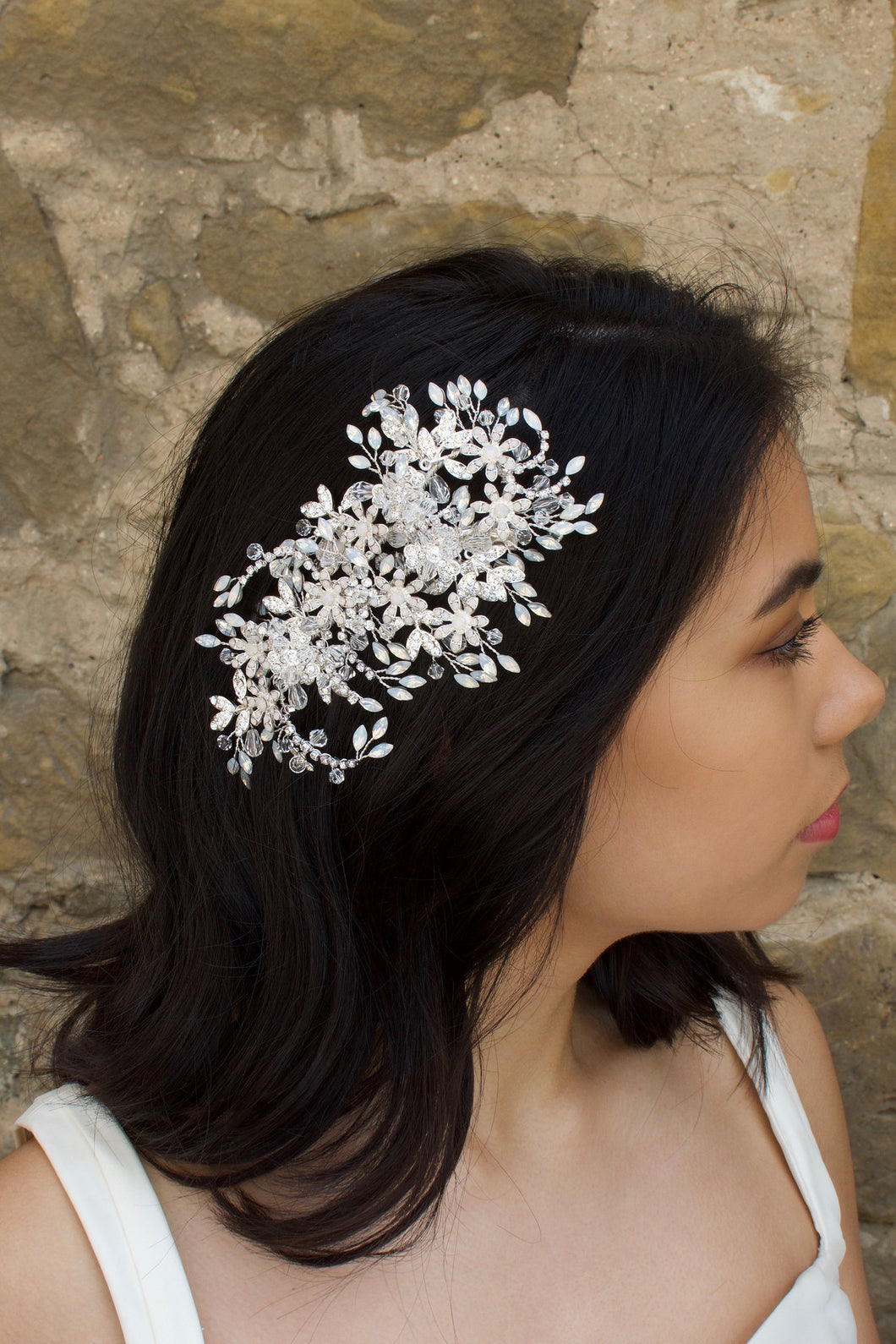 Model wears a large silver side comb on her dark hair with a stone wall background