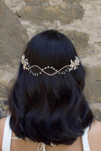 Load image into Gallery viewer, A Black haired model with her hair down wears a soft bridal vine at the back of her head. Stone wall background