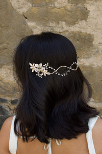 A Black haired model with her hair down wears a Silver soft bridal vine at the back of her head. Stone wall background