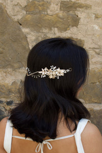 A Black haired model with her hair down wears a soft gold bridal vine at the back of her head. Stone wall background