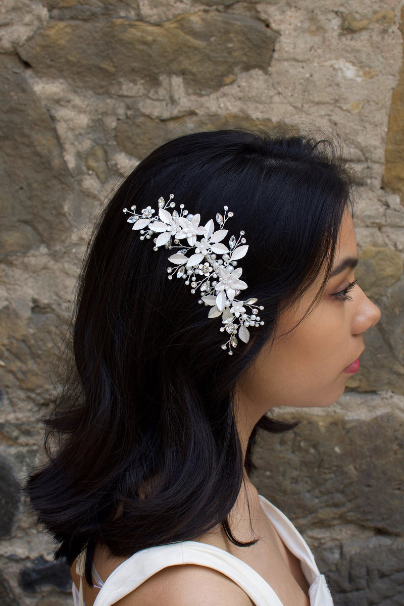 Dark haired model with long hair wears a side comb of silver leaves at the side of her head.