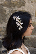 Load image into Gallery viewer, Dark haired model with long hair wears a side comb of pale gold leaves at the side of her head. With a stone wall background