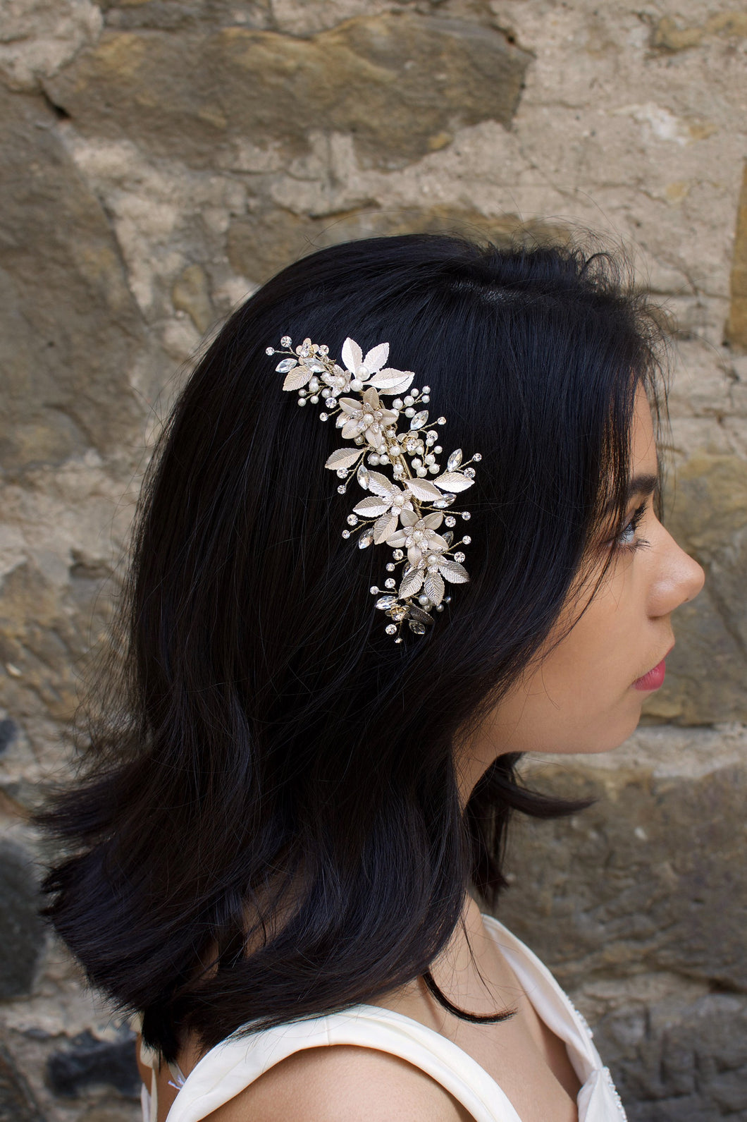 Dark haired model with long hair wears a side comb of pale gold leaves at the side of her head. With a stone wall background