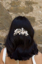 Load image into Gallery viewer, Dark haired model with long hair wears a side comb of pale gold leaves at the back of her head. With a stone wall background