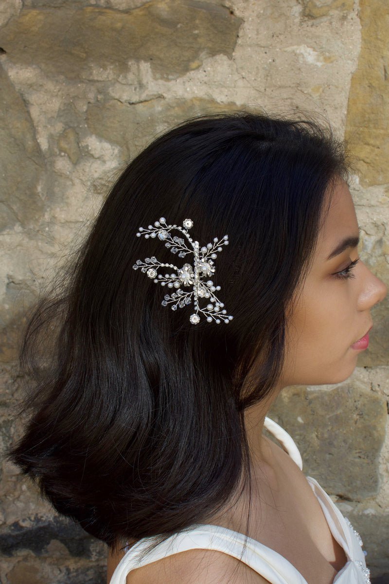 A long hair model with a silver and pearl side comb with a stone wall background