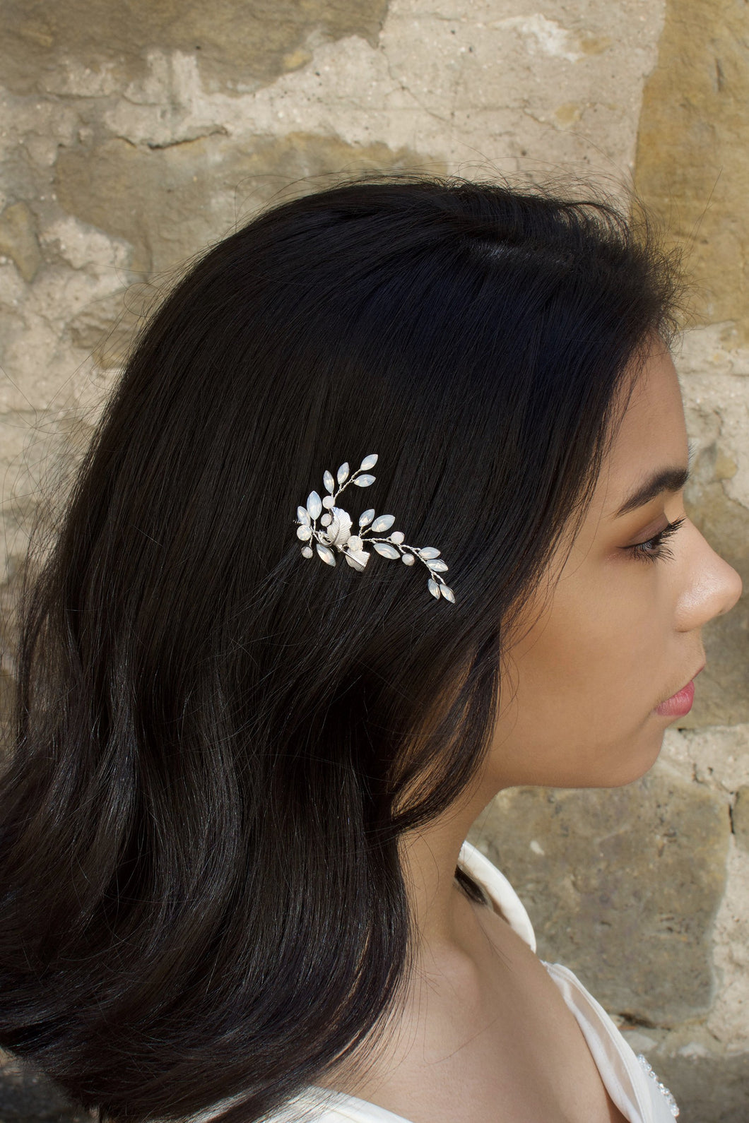 A dark haired model with long hair wears a small leaves bridal hair pin. In the background is a stone wall.