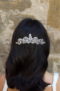 Model with long black hair wears a silver crystal comb at the back of her head in front of an old stone wall