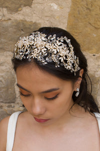 A model wears a wide golden headband across the front of her head with a stone wall background