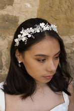 Load image into Gallery viewer, Dark hair model wears a headband of ceramic flowers  and pearls with a wall background