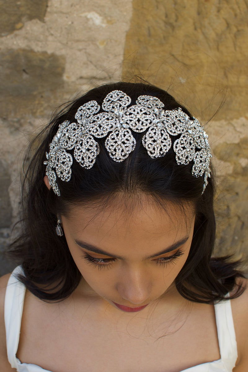 A front view of a wide silver headband worn by a dark hair model with a stone wall backdrop