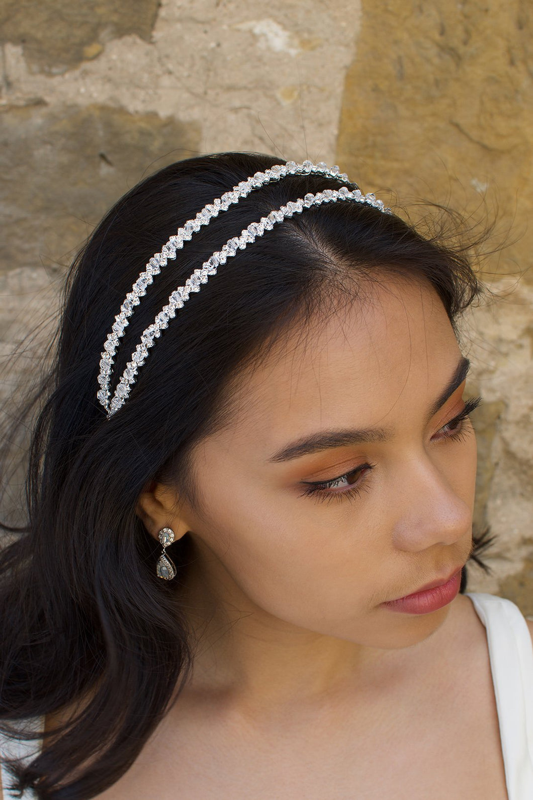 Black hair bride wearing a simple two row silver headband with a stone wall background.