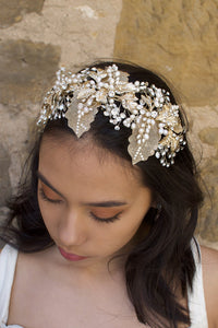 A wide gold headband worn by a dark hair bride with a stone background
