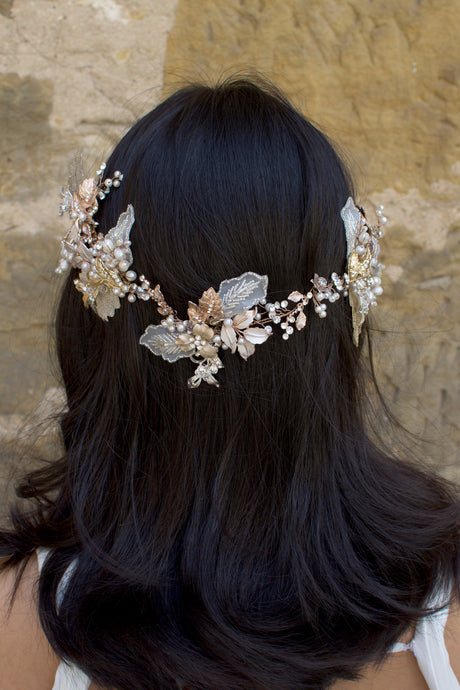 A dark haired model with hair down wears a Bridal Vine in Silver, Gold and Rose Gold with a background of a stone wall
