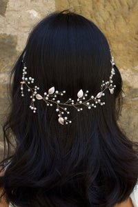 The back of a black haired model wearing a very fine wire bridal vine with leaves and pearls