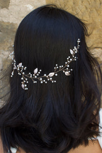 A dark haired Bride wears a thin wire Bridal Vine with leaves and pearls.