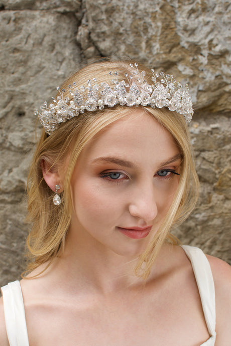 A Silver Flowers and pearls wide tiara worn by a blonde bride with a stone wall background.