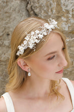 Load image into Gallery viewer, A blonde Bride wears a headband of ceramic flowers and pearls with a stone wall background