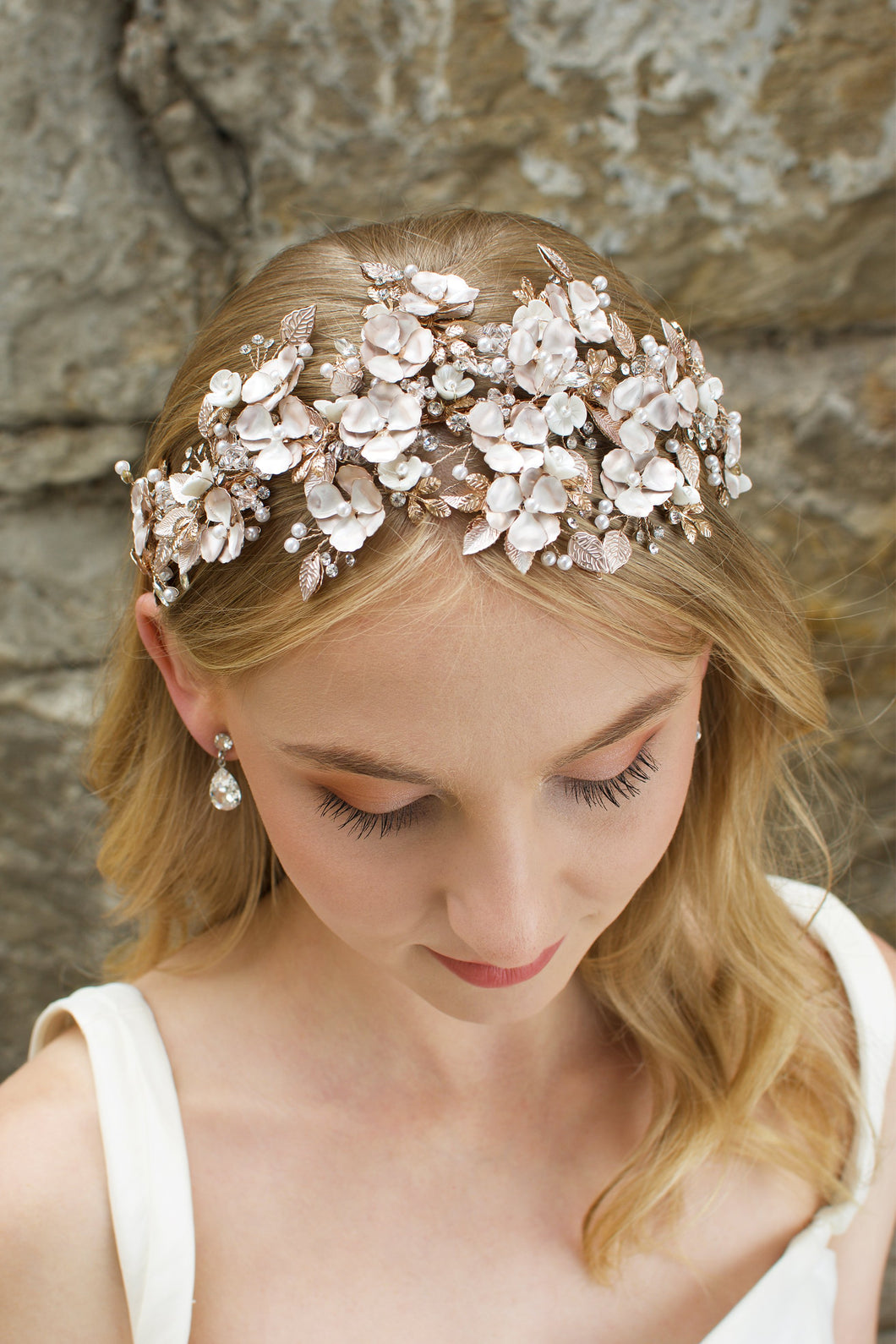Blonde  Haired model wears a wide headband of flowers with the background of a stone wall