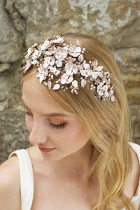 Blonde  model wears a wide headband of flowers with the background of a stone wall
