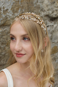 Blonde Bride with green eyes wears a double row bridal headband in gold with a stone wall background