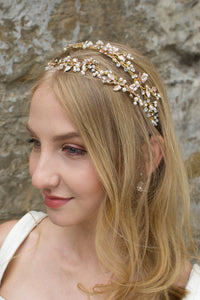 Blonde smiling bride wearing a gold and pearl headband with a stone wall backgtound