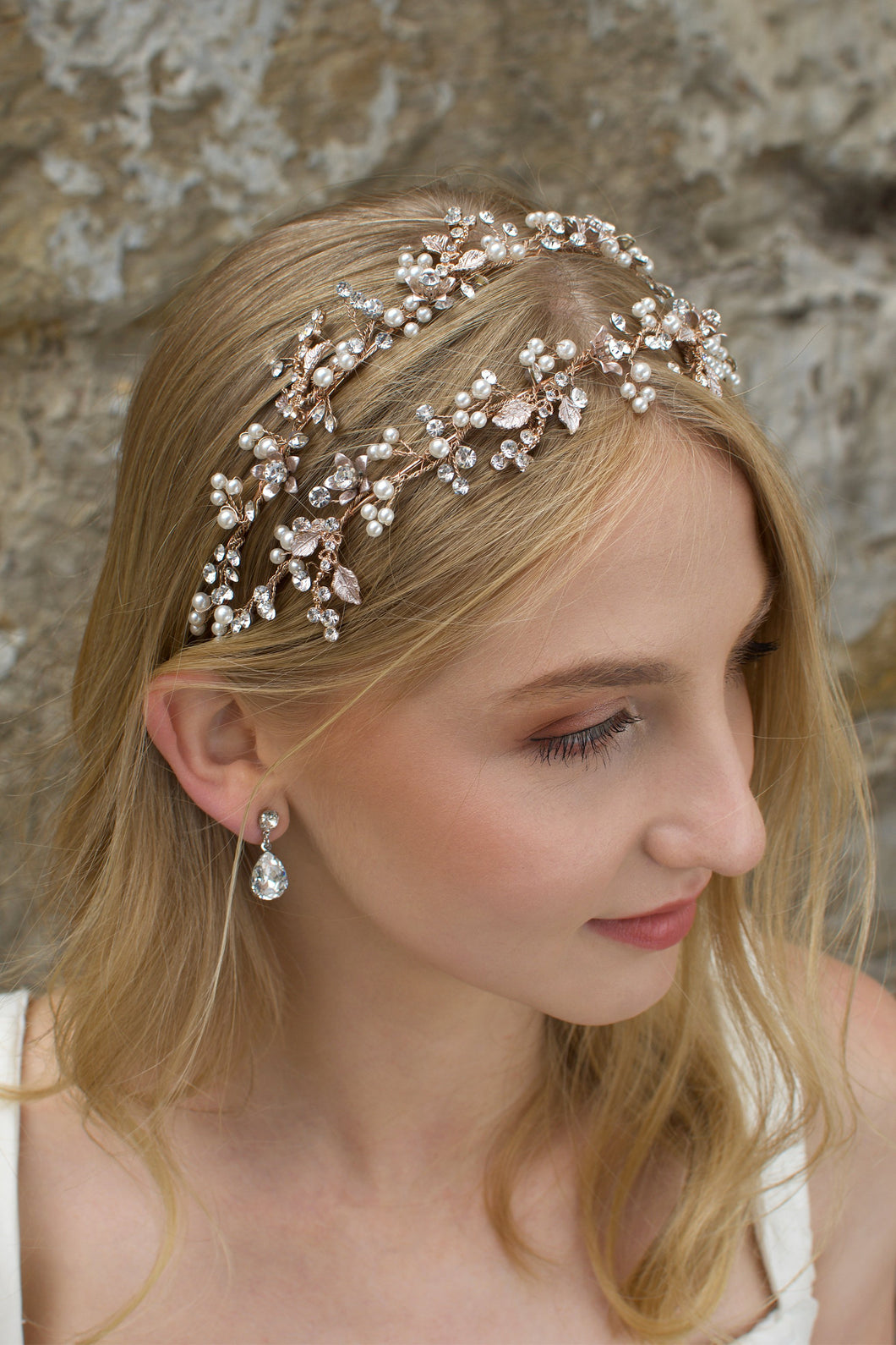 Double row headband in rose gold worn by a blonde model with a stone wall background