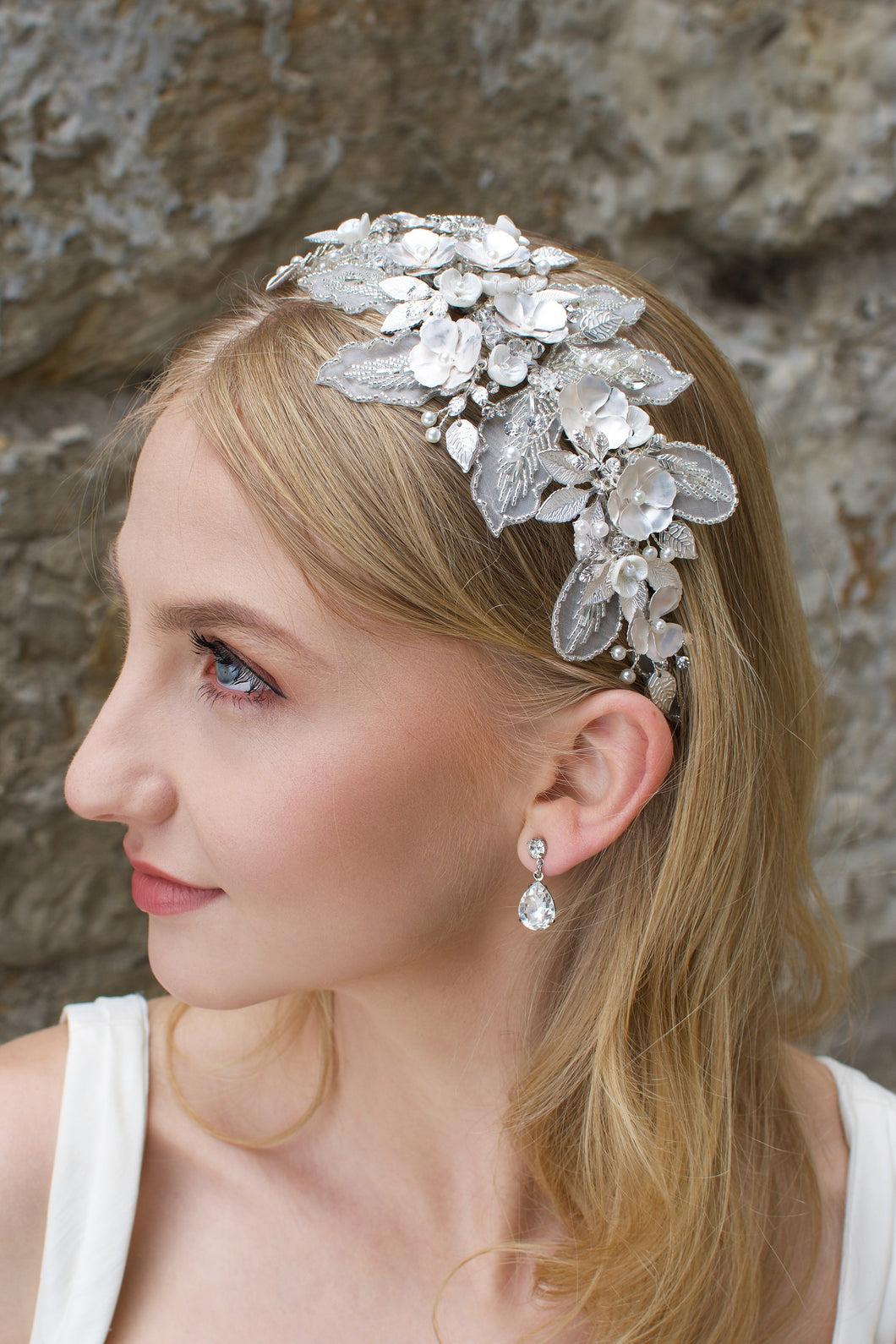 Blonde bride wearing a lace and flower headband with a stone wall backdrop