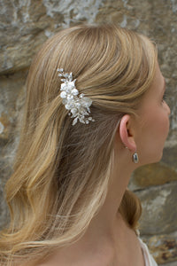 Blonde model wears a small silver flower clip in front of a stone wall