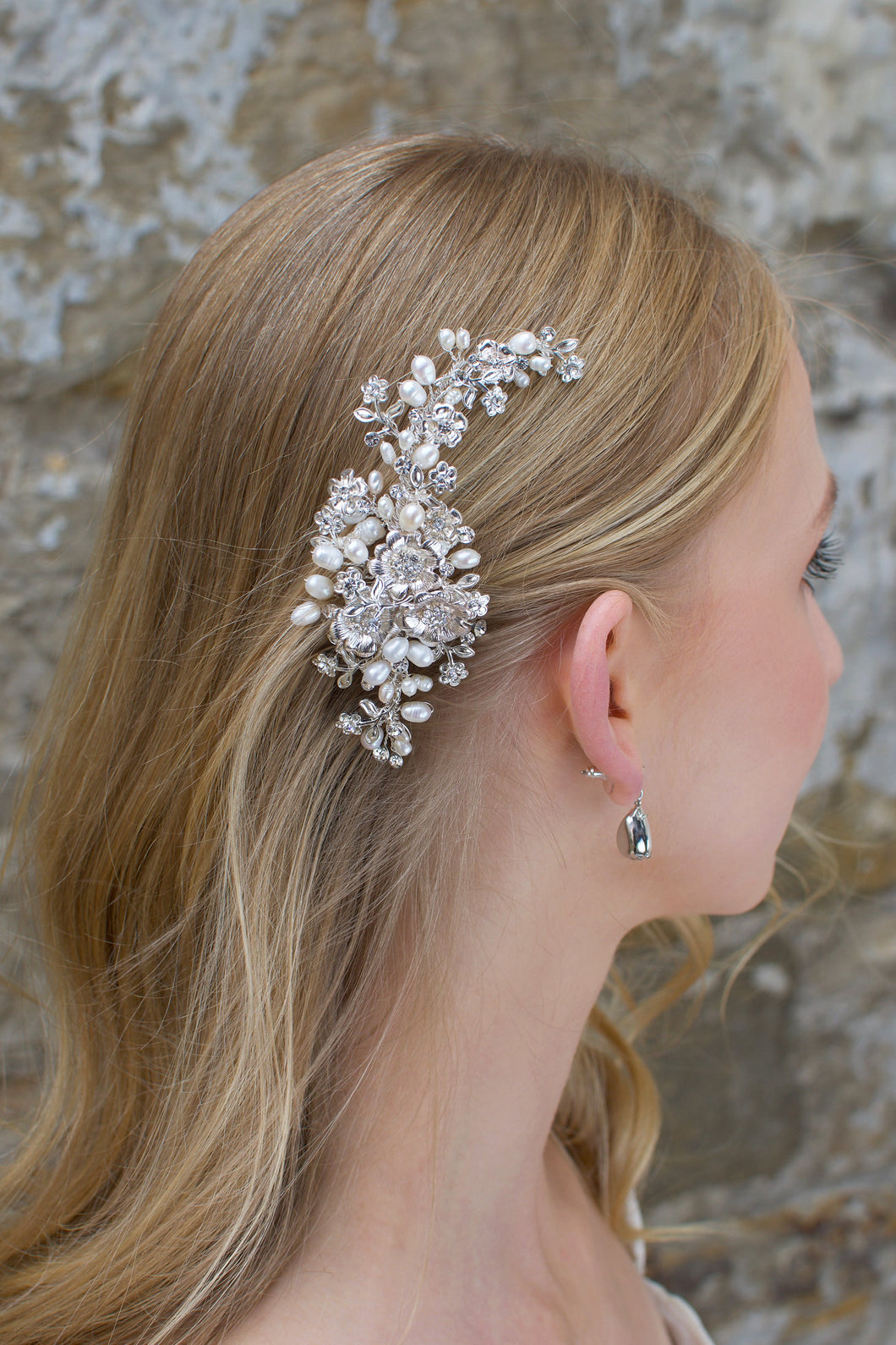 Freshwater pearl and silver side comb worn by a blonde bride
