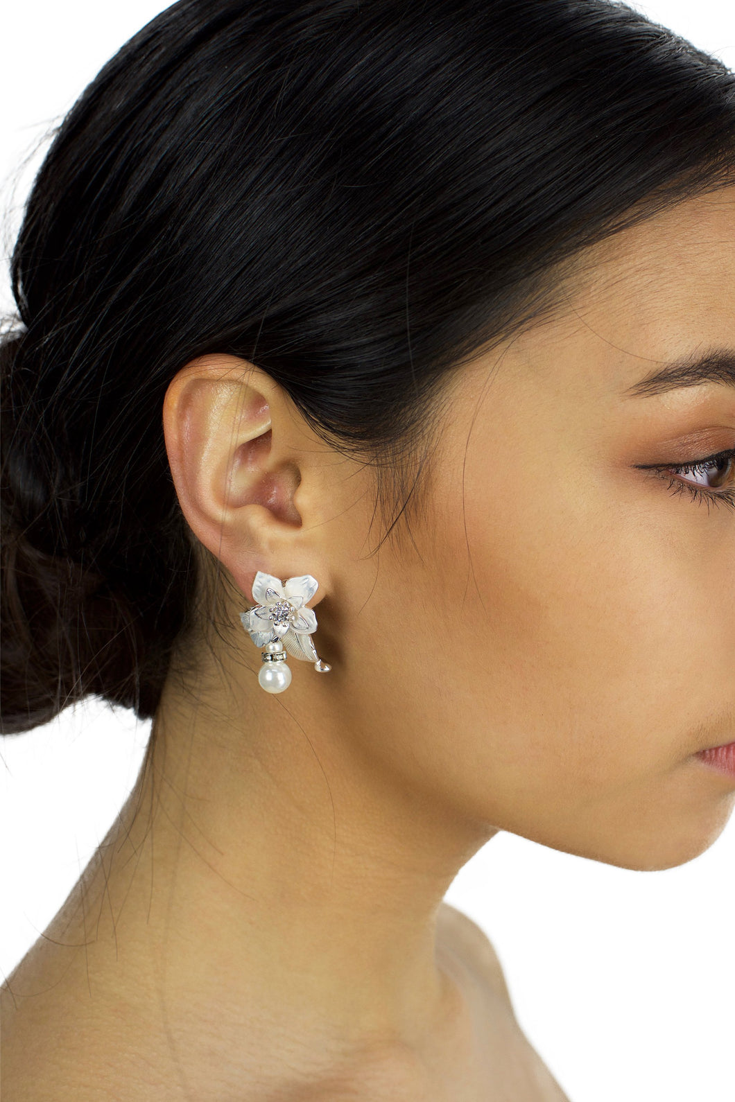 Flower and pearl soft silver earring worn by a dark haired bridal model