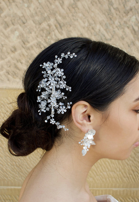 Clear Crystals headpiece on the side of a dark hair model wearing a white flower earring with a stone wall background