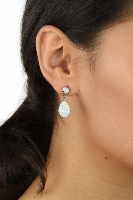 Dark hair model wears a silver earring with a white opal stone