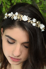 Load image into Gallery viewer, White Flowers and gold leaves headband worn at the front of a dark hair model's head with pine tree background